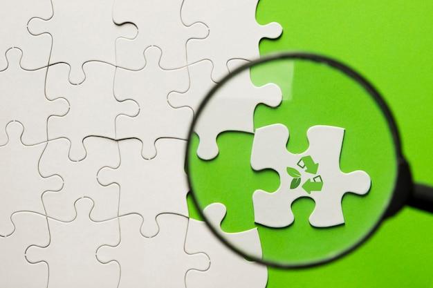 Loupe masse sur puzzle blanc avec l'icône de recyclage sur la surface verte