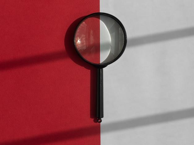Loupe noire sur fond blanc et rouge avec des ombres de la lumière du jour. outil de recherche.