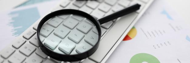 Une loupe noire se trouve sur un clavier d'ordinateur portable blanc