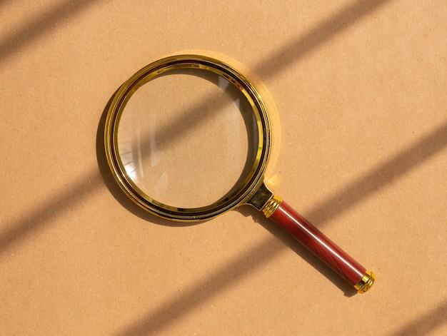 Loupe d'or sur fond marron artisanal avec lumière du jour. concept d'outil de recherche.