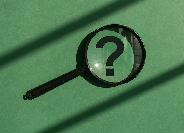 Loupe avec point d'interrogation à l'intérieur sur fond vert concept d'étude d'analyse trouvant et...