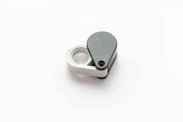 Loupe pour les diamants ou voir l'amulette isolée sur un fond blanc.