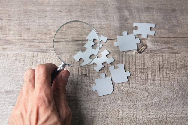 La loupe regarde les pièces du puzzle sur la table