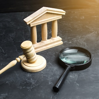 Une loupe se trouve près du palais de justice verdict des poursuites et projets de loi cour constitutionnelle obstruction aux droits de l'homme contrôle du pouvoir et transparence