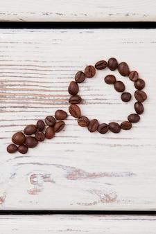 Loupe en verre faite de grains de café torréfiés. le concept de trouver du café. surface en bois blanc.