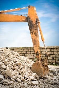 Lourde excavatrice d'organge avec pelle debout sur la colline avec des rochers