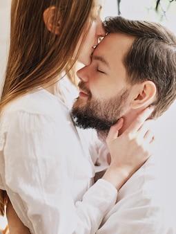 Love girl embrasse son petit ami sur le front. embrasser doucement baiser. habillé en pyjama