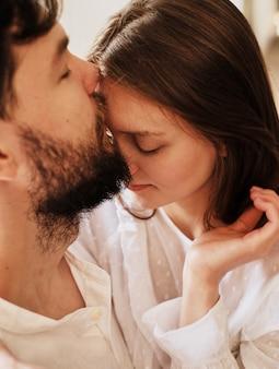 Lover boy embrasse sa petite amie sur le front. embrasser doucement baiser. habillé en pyjama