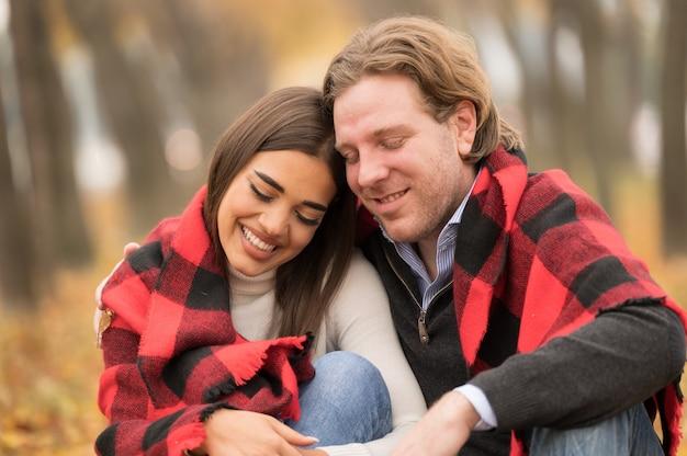 Loving caucasian couple hugging avec une couverture sur eux assis dans la forêt d'automne