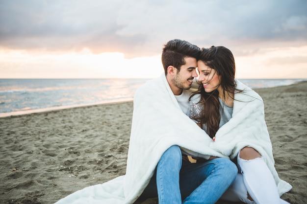 Loving couple assis sur une plage couverte par une couverture blanche