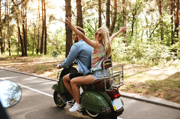 Loving couple man on scooter with womanfriend outdoors