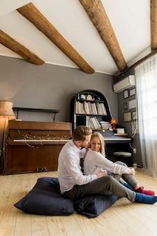 Loving jeune couple assis sur le sol dans la chambre