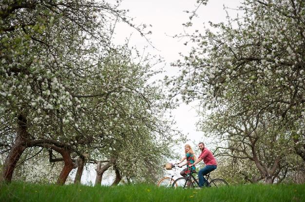 Loving jeune couple à vélo dans le jardin de printemps