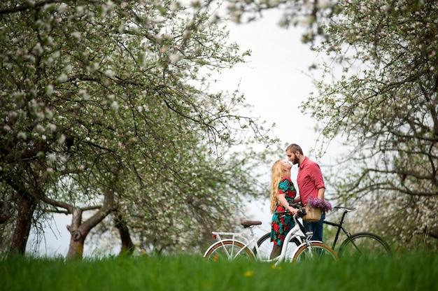 Loving jeune couple avec des vélos dans le jardin de printemps