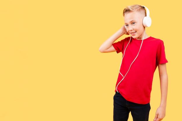Low angle jeune garçon écoute de la musique
