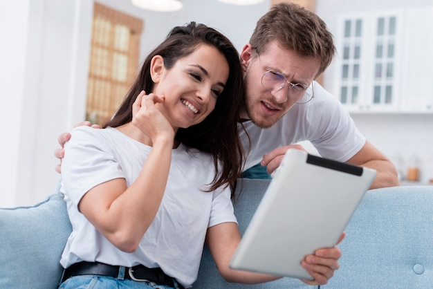 Low angle man and woman looking on tablet