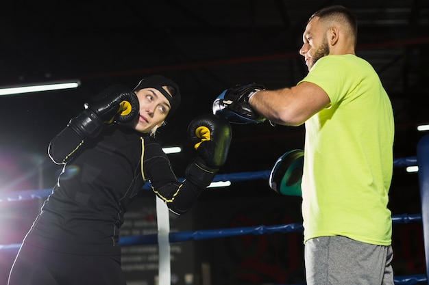 Low angle of female boxer pratiquant avec male trainer in the ring