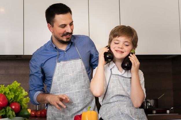 Low angle père et fils jouant avec des légumes