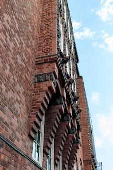 Low angle shot vertical d'un bâtiment rouge sous le beau ciel nuageux