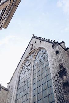 Low angle shot vertical d'un vieux bâtiment en brique sous le ciel nuageux