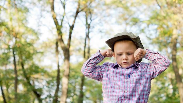 Low angle view of an bouleversé petit garçon fronçant les sourcils avec ses mains serrées dans les poings de chaque côté de son front à l'extérieur dans les bois
