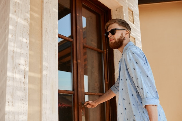 Low angle view of beau jeune homme mal rasé à la mode portant des lunettes de soleil