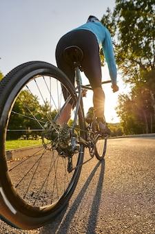 Low angle view of coureur cycliste masculin professionnel chevauchant son vélo de route dans le parc au coucher du soleil