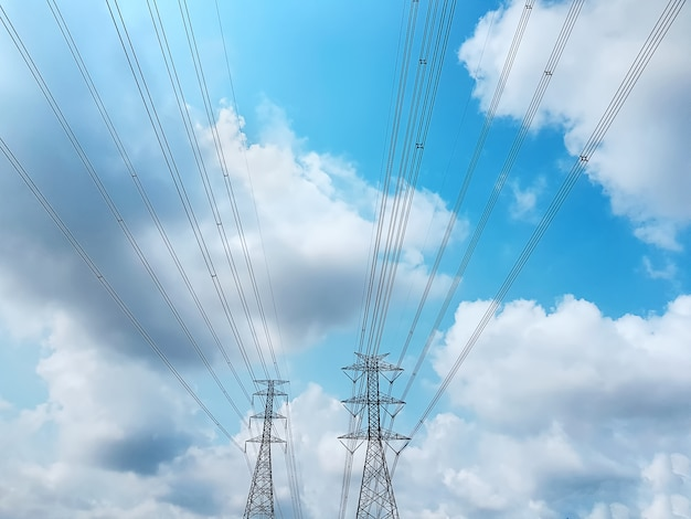Low angle view of high voltage towers and power lines against blue cloudy sky