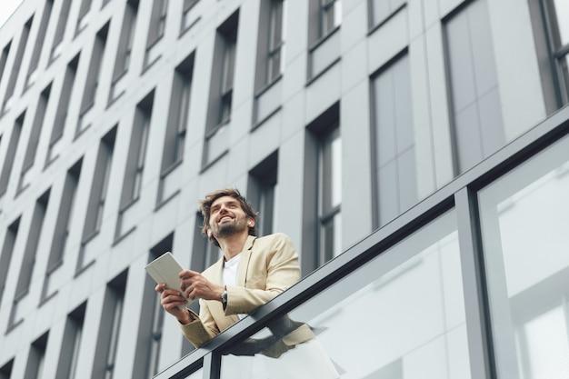 Low angle view of smiling entrepreneur barbu à l'aide de tablette numérique à l'extérieur de son propre bureau