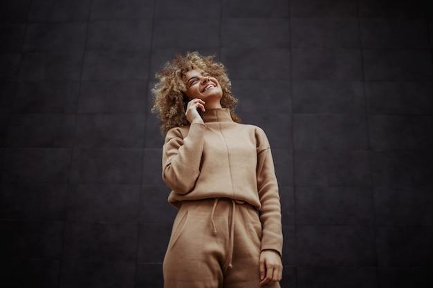 Low angle view of smiling trap girl en survêtement debout et ayant un appel téléphonique avec un ami.