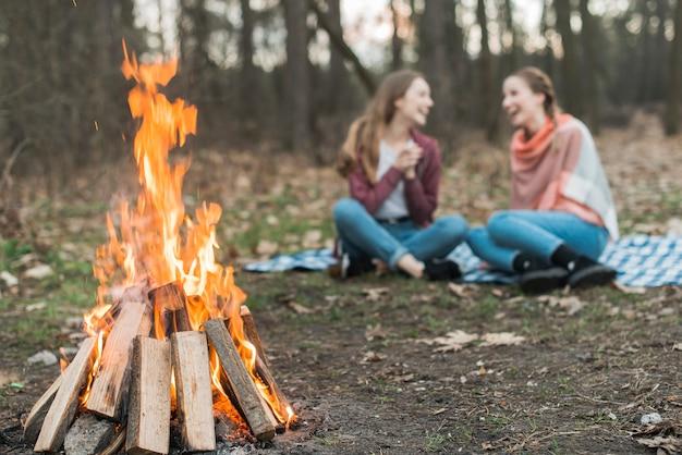 Low angle woman camping avec feu de joie