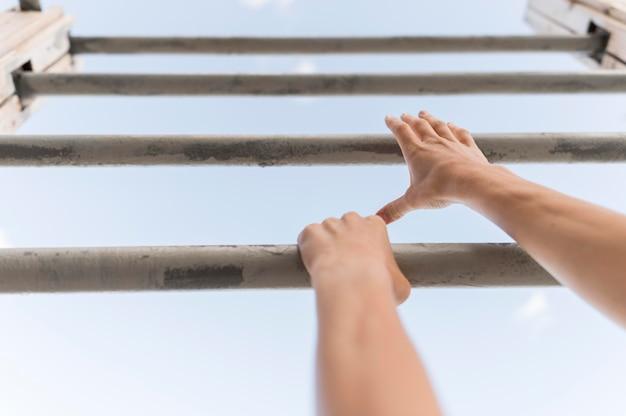 Low angle woman escalade sur des barres métalliques
