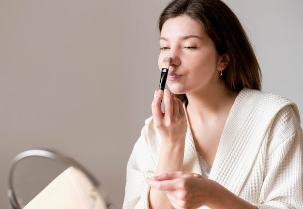 Low angle woman using brush for foundation