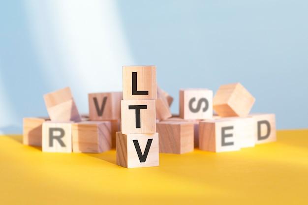 Ltv écrit sur des cubes en bois - disposés en pyramide verticale, fond gris et jaune, ltv - abréviation de valeur à vie, concept d'entreprise