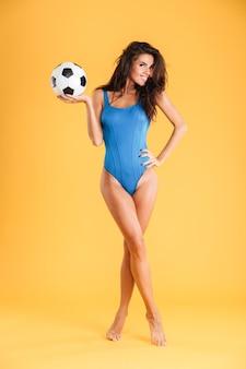 Ludique assez sportive souriante jeune femme en maillot de bain bleu posant tenant ballon isolé sur le mur orange