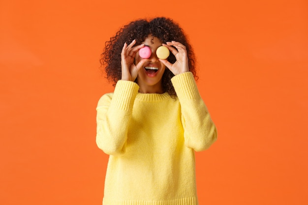 Ludique, drôle et insouciante, jolie fille bouclée afro-américaine en pull jaune, fou de faire des yeux de macarons et souriant, manger des bonbons, comme des desserts, debout orange