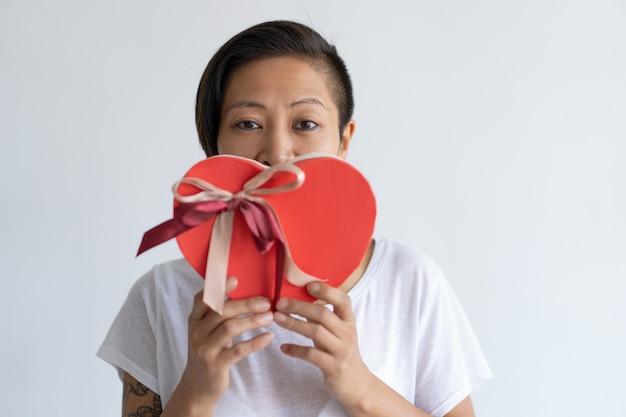 Ludique femme tenant une boîte cadeau en forme de coeur devant la bouche