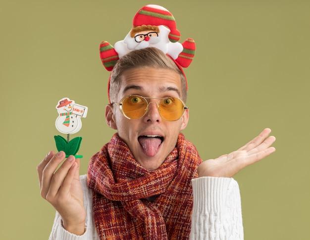 Ludique jeune beau mec portant bandeau et écharpe du père noël regardant la caméra tenant le jouet de bonhomme de neige montrant la main vide et la langue isolée sur fond vert olive