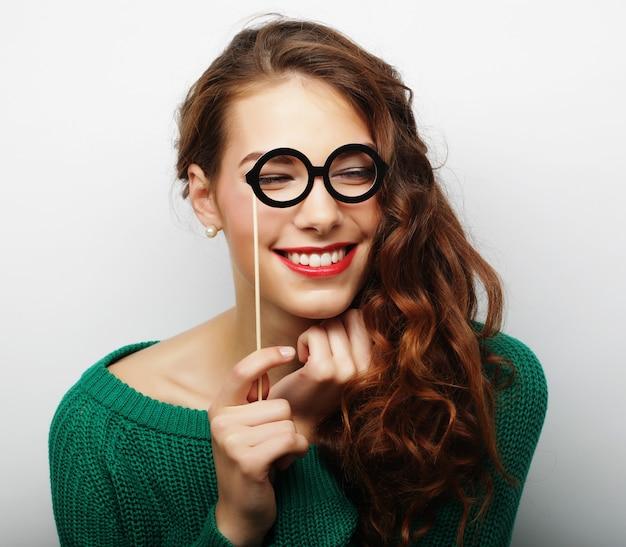 Ludique jeune femme tenant des lunettes de fête