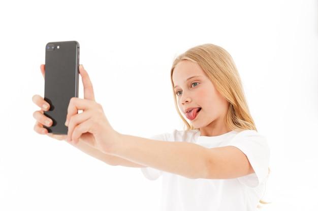 Ludique jeune fille blonde dans des vêtements décontractés faisant selfie sur smartphone sur blanc