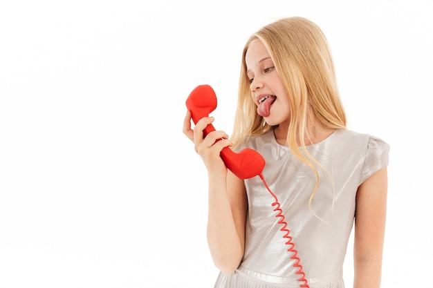 Ludique jeune fille blonde en robe parlant par téléphone et montrant sa langue sur blanc