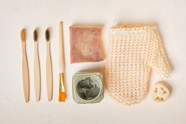 Luffa, savon, argile bleue dans un bocal en verre, brosse, gant de toilette et brosses à dents en bambou sur fond beige, espace copie