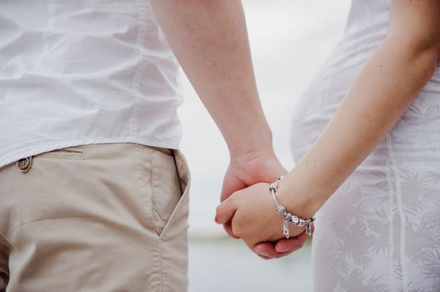 Lui et elle se tiennent par la main. un homme tient la main d'une femme. femme enceinte.
