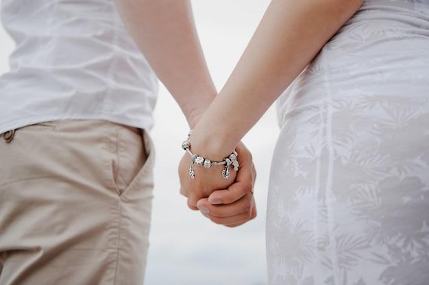 Lui et elle se tiennent par la main. un homme tient la main d'une femme