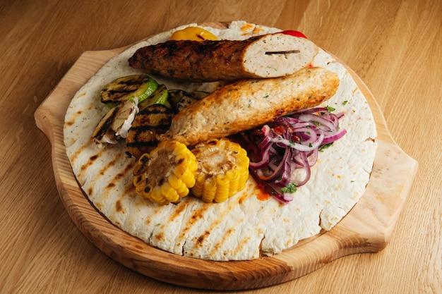 Lula-kebab de poulet aux légumes grillés. servi sur un plateau en bois