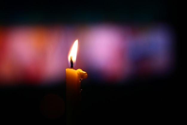 Lumière de bougie avec fond bokeh dans l'obscurité.