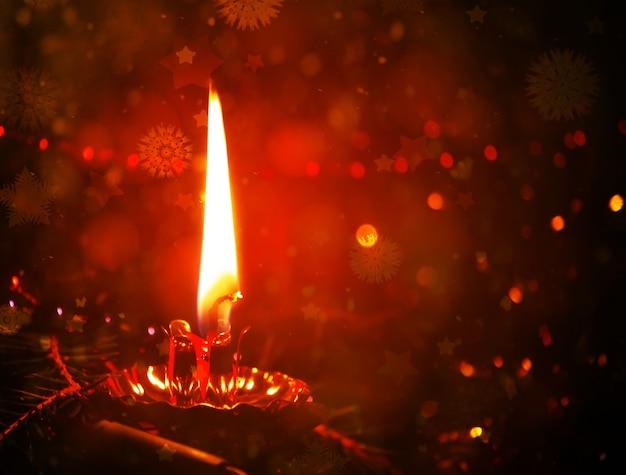 Lumière chaude de flamme de bougie colorée brûlante rouge. effet bokeh pailleté.