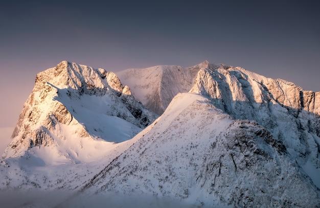 Lumière dorée sur la colline de pic de neige dans la matinée