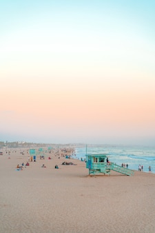 Lumière douce de coucher du soleil de plage de santa monica et personnes marchant sur la bande de plage devant l'océan