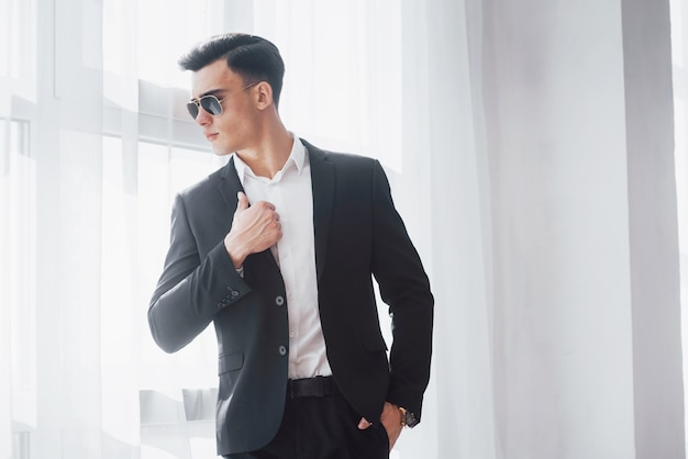 La lumière du jour passe par la fenêtre. portrait de jeune homme élégant en tenue d'affaires classique debout dans la salle blanche.